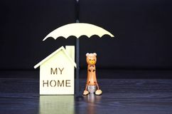 Insurance, an umbrella protects house. Stock Image