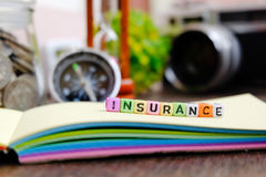 INSURANCE word block on note pad and stethoscope over wooden background Stock Images
