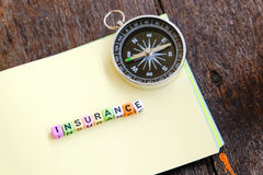 INSURANCE word block on note pad and stethoscope over wooden background Stock Photos