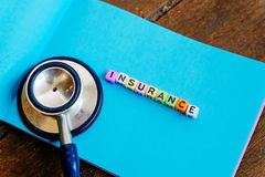 INSURANCE word block on note pad and stethoscope over wooden background Royalty Free Stock Image
