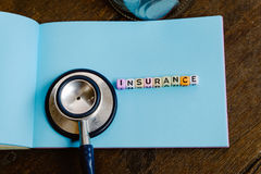 INSURANCE word block on note pad and stethoscope over wooden background Royalty Free Stock Photo