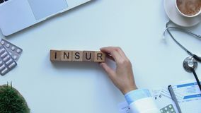 Insurance word on wooden cubes made by doctors hand, health and life, top view. Stock footage stock footage