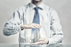 Insure your construction investments. Close up of hands holding image of modern cityscape Royalty Free Stock Image
