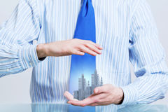 Insure your construction investments. Close up of hands holding image of modern cityscape Royalty Free Stock Photography