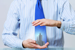 Insure your construction investments. Close up of hands holding image of modern cityscape Royalty Free Stock Photos