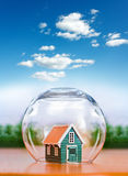 Insured house under glass sphere Royalty Free Stock Photos