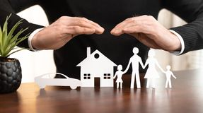Concept of family, home and car insurance. Insurer protecting a family, a house and a car with his hands stock photography