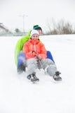 Intégral de jeunes couples sledging sur la neige a couvert la terre Image libre de droits