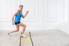 Intégral de la belle jeune femme blonde sportive sportive dans des shorts noirs et du dessus bleu soyez dur travaillant et s'exer photo libre de droits