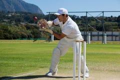 Intégral de la boule de cricket contagieuse de wicketkeeper derrière des tronçons Photos libres de droits