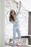 Intégral de la musique de écoute de fille tout en chantant dans la brosse à cheveux sur le lit Photographie stock