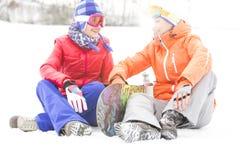 Intégral des amis féminins avec le surf des neiges détendant sur la neige Photographie stock libre de droits
