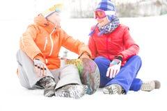Intégral des amis féminins avec le surf des neiges détendant sur la neige Photos stock