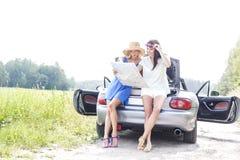 Intégral des amis féminins lisant la carte tout en se penchant sur le convertible dans la campagne Images libres de droits