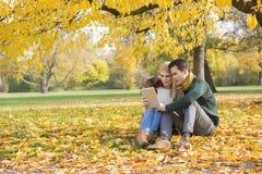 Intégral des couples utilisant la tablette en parc pendant l'automne Photographie stock