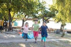 Intégral des enfants tenant des mains et le fonctionnement au parc Image stock