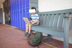 Intégral du garçon employant des verres d'ordinateur portable et de réalité virtuelle tout en se reposant sur le banc image stock