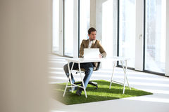 Intégral du jeune homme d'affaires avec l'ordinateur portable au bureau sur le gazon dans le nouveau bureau Photos stock