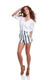 Intégral du sourire jeune amincissez la femelle bronzée dans des shorts de denim Image libre de droits