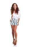 Intégral du sourire jeune amincissez la femelle bronzée dans des shorts de denim Images stock