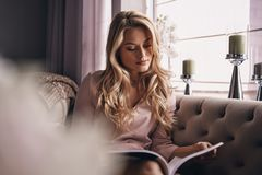 intéresser Magazine attrayante de lecture de jeune femme tandis que reposez-vous photo libre de droits