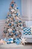 Intérieur à la maison de Noël - un fauteuil confortable et un sapin décoré dans des couleurs blanches bleues Photos libres de droits