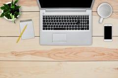 Intérieur à la maison Vue supérieure de bureau en bois avec l'ordinateur portable, le téléphone portable, le carnet vide pour le  Images libres de droits