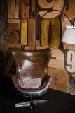 Intérieur élégant dans le style de grenier plâtre texturisé gris sur les lettres en bois de mur fauteuil confortable fait de cuir photos stock