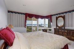 Intérieur élégant de chambre à coucher avec la literie blanche et les oreillers rouges photo stock