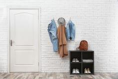 Intérieur élégant de couloir avec la porte, le support de chaussure et les vêtements accrochant sur le mur images stock
