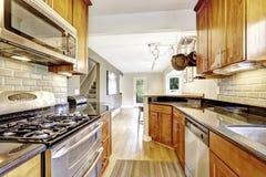 Intérieur étroit de pièce de cuisine avec des Cabinets et des appareils d'acier Photographie stock libre de droits