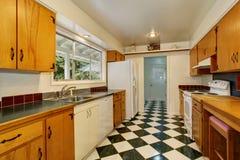 Intérieur étroit de pièce de cuisine avec la tuile de coffrets, blanche et noire brun clair Photographie stock