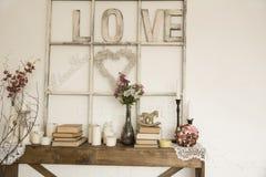 Intérieur avec un amour, des livres, des fleurs et des bougies d'inscription Image stock