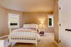 Intérieur beige simple de chambre à coucher avec la moquette et deux fenêtres photographie stock