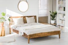 Intérieur blanc de chambre à coucher avec le lit grand en bois, vert frais pl photographie stock libre de droits