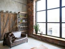 Intérieur brutal dans une couleur brune foncée avec un sofa en cuir et une grande fenêtre images stock