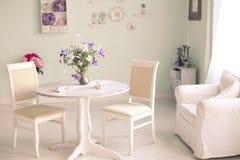 Intérieur chic minable de salle à manger avec les plats décoratifs de fleurs photo stock