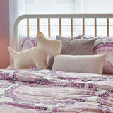 Intérieur confortable de chambre à coucher avec la poupée de chiot et les oreillers roses sur le lit Image libre de droits