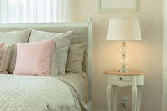 Intérieur confortable de chambre à coucher avec les oreillers et la lampe de lecture roses sur la table de chevet Images stock