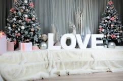 Intérieur confortable de nouvelle année avec un grand voile de peluche, deux arbres de Noël, animaux de forêt de jouet et l'amour Photo stock