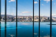 Intérieur contemporain avec la vue de piscine et de ville Grande surface de l'eau photographie stock libre de droits