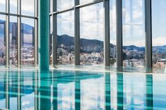 Intérieur contemporain avec la vue de piscine et de ville Grande surface de l'eau images stock