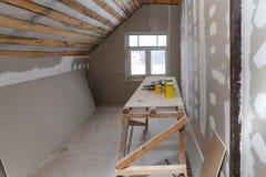 Intérieur d'appartement de pièce avec la nouvelle fenêtre et l'échafaudage fait maison de matériaux, outils, niveau pendant sur l image stock