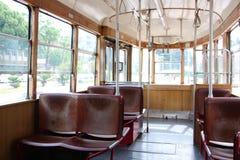 Intérieur d'un vieux tram de vintage de tourisme À l'intérieur de est les sièges rouge-brun vides et en bois Par les vitraux vous Image stock