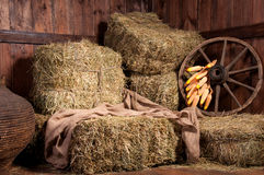 Intérieur d'une ferme rurale - foin, roue, maïs. Image libre de droits