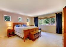 Intérieur de chambre à coucher avec la moquette beige et les rideaux bleu-foncé image libre de droits