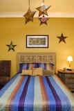 Intérieur de chambre à coucher avec le couvre-lit rayé et les décorums Photographie stock libre de droits