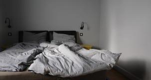 Intérieur de chambre à coucher avec le lit qui n'est pas encore fait banque de vidéos