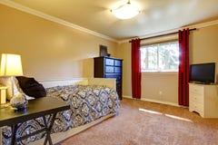 Intérieur de chambre à coucher avec les murs et la TV jaunes. Photographie stock