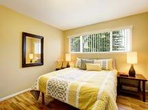 Intérieur de chambre à coucher dans des tons jaunes avec le plancher en bois dur Images libres de droits